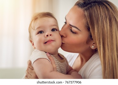 Beautiful young mom having fun with her cute baby boy at the home. She is kissing baby.