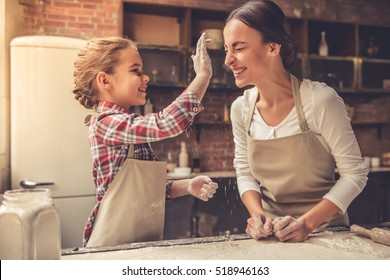 Beautiful young mom and her cute little daughter are playing and smiling while baking in kitchen at home