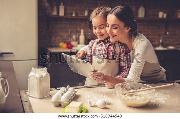 Beautiful young mom and her cute little daughter are using a digital tablet and smiling while baking in kitchen at home