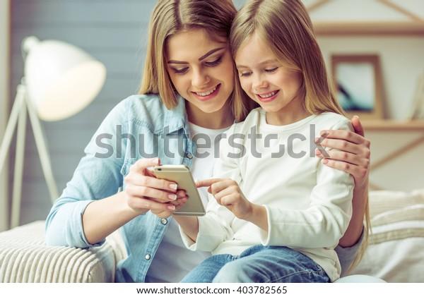 美しい若い母親と娘は、家でソファに座りながら、スマートフォンを使って微笑んでいる