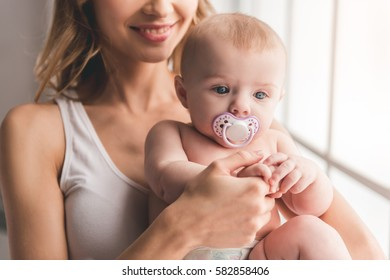 Beautiful young mom is holding her cute baby in arms and smiling while standing near the window