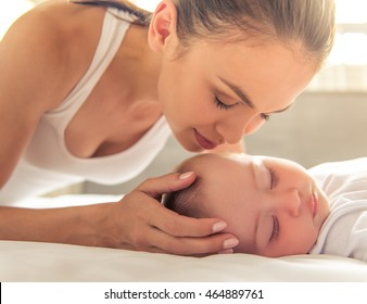 Beautiful young mom is kissing her cute little baby who is sleeping in bed at home, close-up
