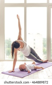 Beautiful young mom in sports wear is smiling while doing yoga with her charming little baby on a mat against window
