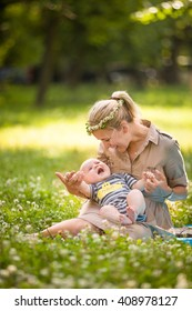 Beautiful young mother with adorable baby boy relaxing sitting on grass on background summer meadow. Summer outdoor portrait of happiness. mother with child in the park on the wild flowers meadow.