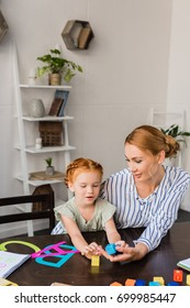 beautiful young mother and adorable daughter learning alphabet at home