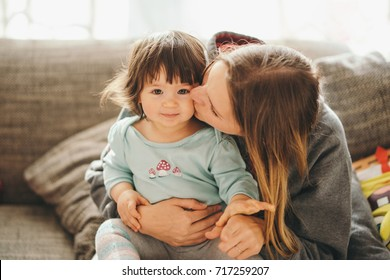 beautiful young mother with adorable little daughter kissing