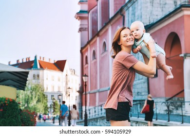 Beautiful young mother with baby child spend time in the old town of Ljubljana, Slovenia, Europe. Mother and son are traveling and walking in a european city.