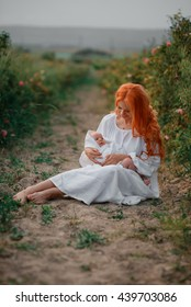beautiful young mother with a baby in her arms outdoors