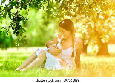 Beautiful young Mother and baby in park portrait. A happy mother looks at the child.