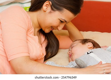Beautiful young mother in bed smiling at her sleeping baby.