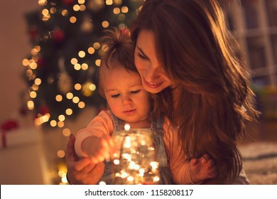 Beautiful young mother and daughter sitting on the floor next to a Christmas tree, hugging and holding a jar of Christmas lights