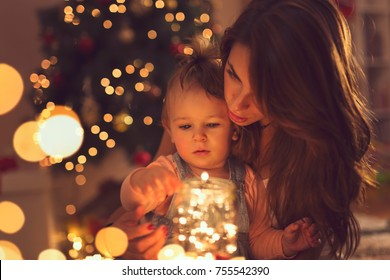 Beautiful young mother and daughter sitting on the floor next to a Christmas tree, hugging and holding a jar of Christmas lights.
