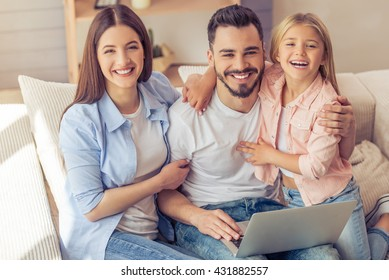 Beautiful young mother, father and their daughter are using laptop, looking at camera and smiling while sitting on the sofa at home