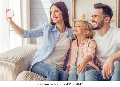 Beautiful young mother, father and their daughter are making selfie using a phone and smiling while sitting on the sofa at home