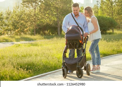 beautiful and young mother and father walking in the park baby in a stroller