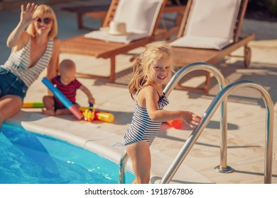 Schöne junge Mutter, die sich beim Spielen mit ihren Kindern am Schwimmbad amüsiert und den heißen Sommertag im Freien genießt