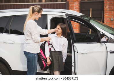 Beautiful young mother helping daughter to get out of car and put on school bag