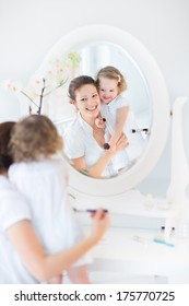 Beautiful young mother and her adorable toddler daughter applying make up together in a beautiful white sunny bedroom with an old elegant mirror