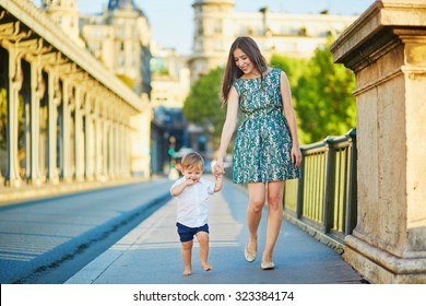 Beautiful young mother with her adorable little son on the Bir Hakeim bridge in Paris, France