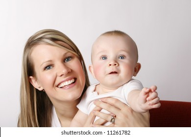Beautiful young mother with her baby boy. Red, Sofa