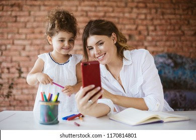 Beautiful young mother and her baby daughter happily taking photos on cellphone with book and felt-tip pens near on desk at cozy home. Family values