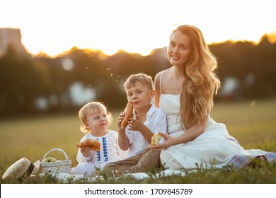 Beautiful young mother with her children, a boy and a girl in a field on a picnic. Heat. Beautiful family in the sunset rays. Summer.