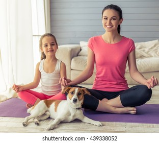 Beautiful young mother and her cute little daughter are looking at camera and smiling while sitting in lotus pose with their dog on yoga mat at home