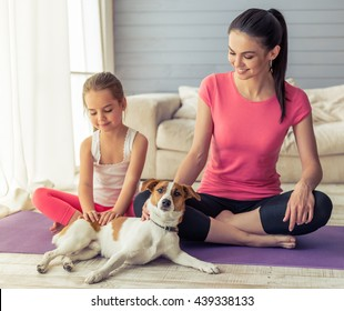 Beautiful young mother and her cute little daughter are patting their dog and smiling while sitting in lotus pose on yoga mat at home
