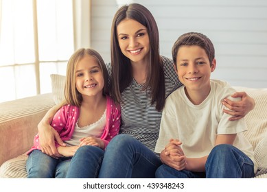 Beautiful young mother, her cute little daughter and son are looking at camera and smiling, sitting on sofa at home