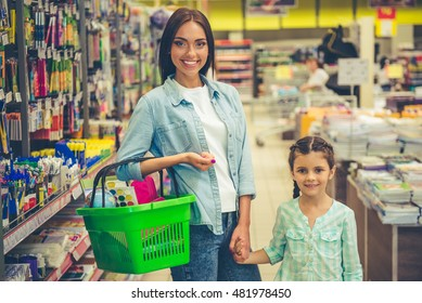 Beautiful young mother and her cute little daughter are holding hands, looking at camera and smiling while choosing school stationery in the supermarket