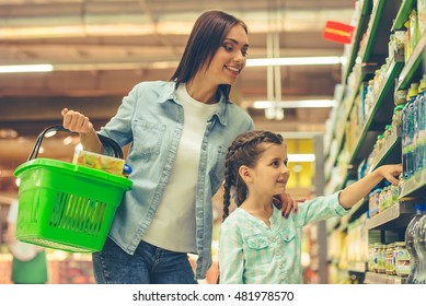 Beautiful young mother and her cute little daughter are smiling while choosing food in the supermarket