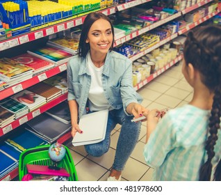 Beautiful young mother and her cute little daughter are smiling while choosing school stationery in the supermarket