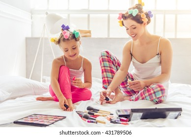 Beautiful young mother and her daughter in pajamas and with hair curlers are doing pedicure and smiling, sitting on bed at home