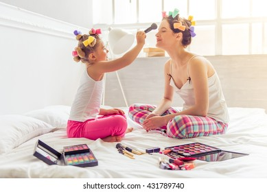 Beautiful young mother and her daughter in pajamas and with hair curlers on bed at home. Cute little girl is doing her mother makeup