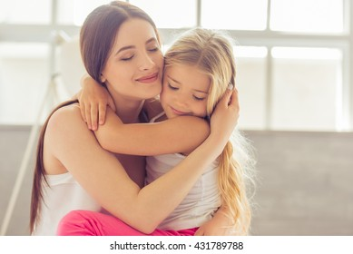 Beautiful young mother and her daughter are hugging and smiling while sitting with closed eyes on the bed at home