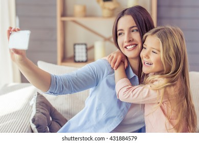 Beautiful young mother and her daughter are making selfie using a phone, hugging and smiling while sitting on the sofa at home