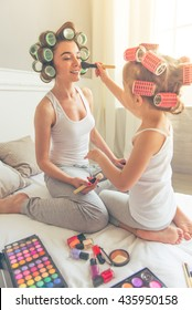 Beautiful young mother and her daughter in pajamas and with hair curlers are sitting on bed at home. Cute little girl is doing her mother makeup