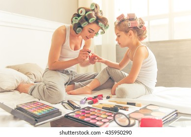 Beautiful young mother and her daughter with hair curlers are sitting on bed at home. Mom is doing her daughter manicure