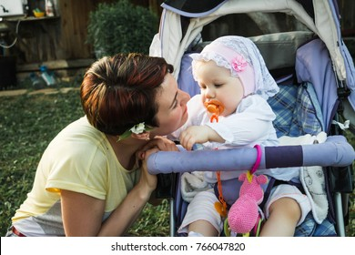 Beautiful young mother with her daughter in stroller in the park in a summer day
