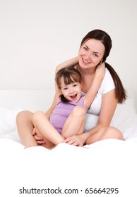 beautiful young mother and her five year old daughter on the bed at home