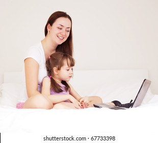 beautiful young mother and her five year old daughter with a laptop on the bed at home