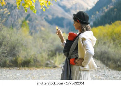 Beautiful young mother with her infant baby in sling outdoor. Mother is carrying her child and travel in autumn