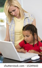 A beautiful young mother and her mixed race young daughter using a laptop at home in the kitchen.