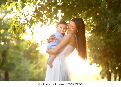 Beautiful young mother holding cute baby boy, outdoors