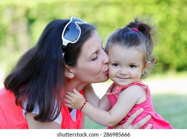 Beautiful young mother kissing her little daughter