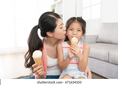 beautiful young mother kissing her lovely little daughter when girl looking at camera eating ice cream enjoying summer day feeling cheerful.