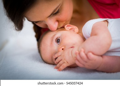 Beautiful young mother kissing and pampering her baby.