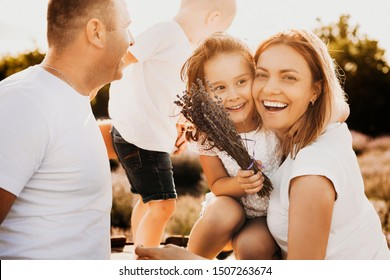 Beautiful young mother laughing while embracing her little daughter when father is looking at their son. Lovely little girl laughing while is near her mother .