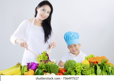 Beautiful young mother and little boy make salad with table full of vegetables