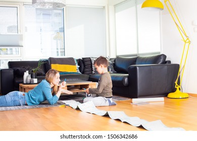 Beautiful young  mother looking at cute son coloring with crayons on paper while laying on the floor in living in room.Family life concept,free time at home